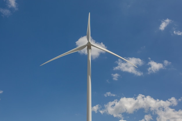 Low angle shot of a windmill under the sunlight and a blue sky at daytime - environmental concept Free Photo
