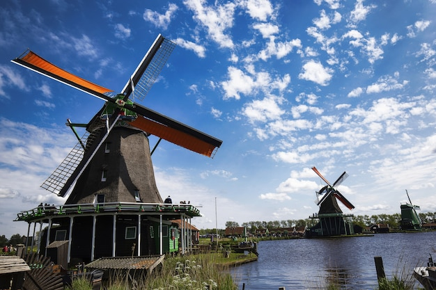 Low angle shot of windmills in zaanse schans neighborhood near the lake in  the netherlands Free Photo