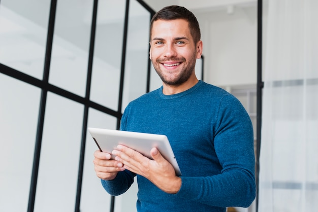 Low angle smilet man with tablet Free Photo