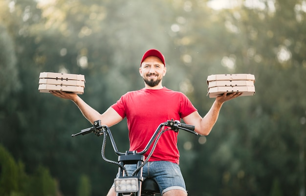 Low angle smiley delivery guy holding pizza boxes Free Photo