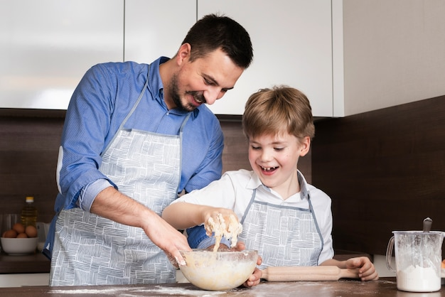 Low angle smiley father and son making dough Free Photo