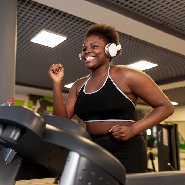 Low angle smiley female running on treadmill Free Photo