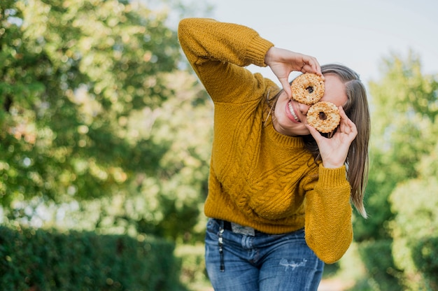 Low angle smiley girl with doughnuts outdoors Free Photo
