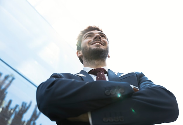Low angle smiley man with crossed arms Free Photo