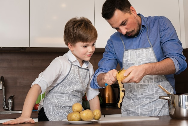 Low angle son and dad cleaning potatoes Free Photo