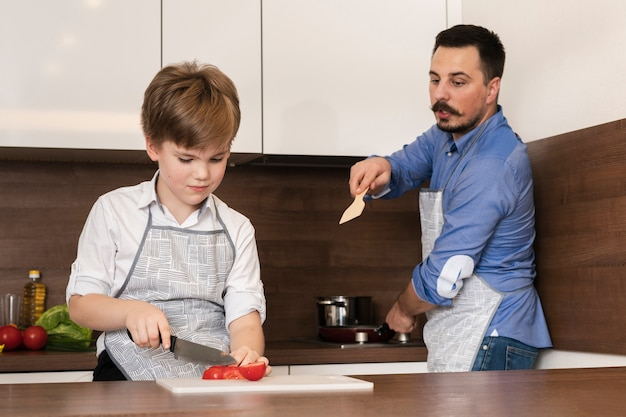 Low angle son and dad cooking Free Photo