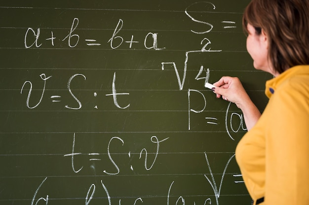 Low angle teacher writing on chalkboard Free Photo