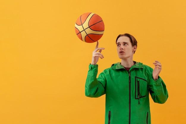 Низкий угол подросток играет с баскетбольным мячом Бесплатные Фотографии