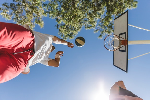 Low angle view of basketball player throwing ball against blue sky Free Photo