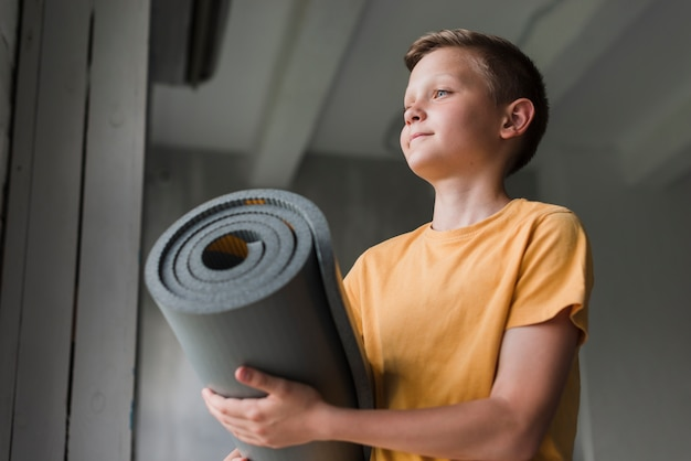 Low angle view of boy holding rolling grey exercise mat Free Photo