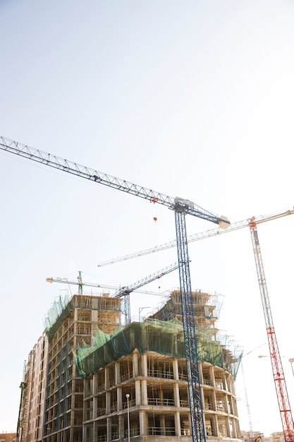 Low angle view of a building with construction crane against blue and white sky Free Photo