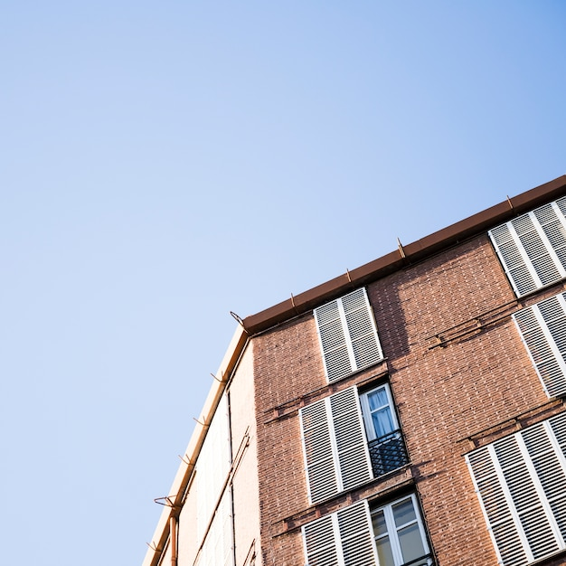 Low angle view of a building with windows against blue sky Free Photo