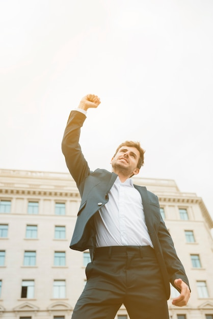Low angle view of a businessman celebrating his success Free Photo