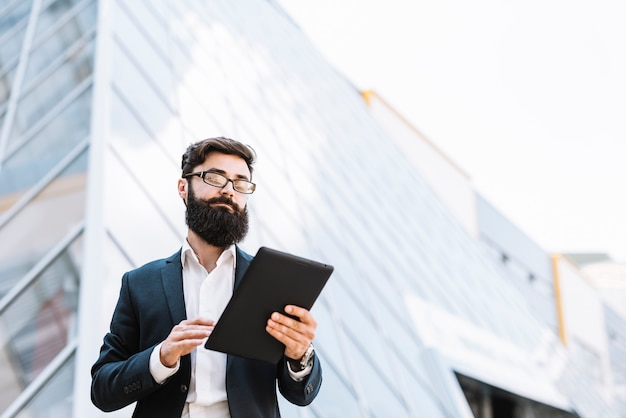 Low angle view of businessman looking at digital tablet standing outside the office building Free Photo