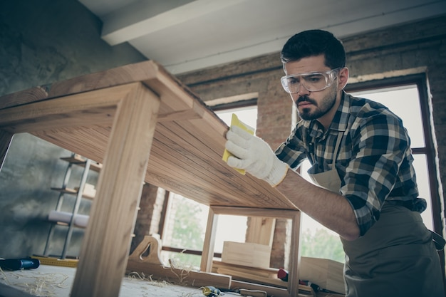 Low angle view  concentrated man hardwood worker renew wooden furniture slab table polish smooth surface in home house garage Premium Photo