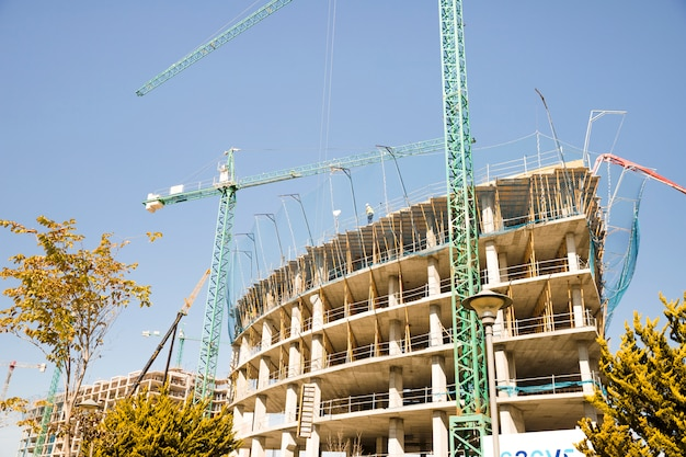 Low angle view of construction crane in front of building Free Photo