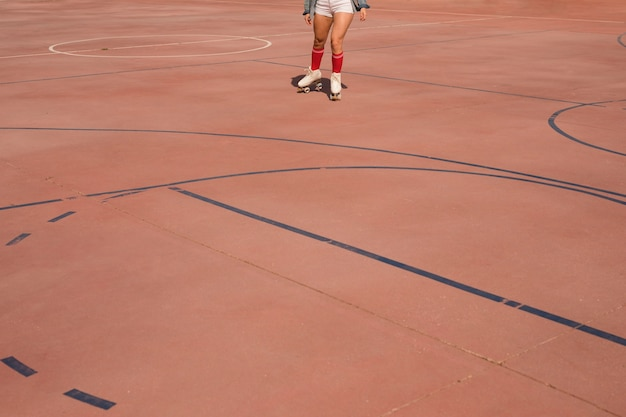 Low angle view of female skater skating on court Free Photo