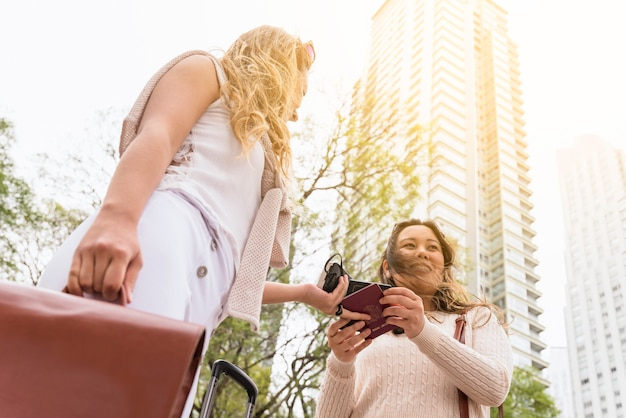 Low angle view of female tourist giving passport to her friend against high rise building Free Photo