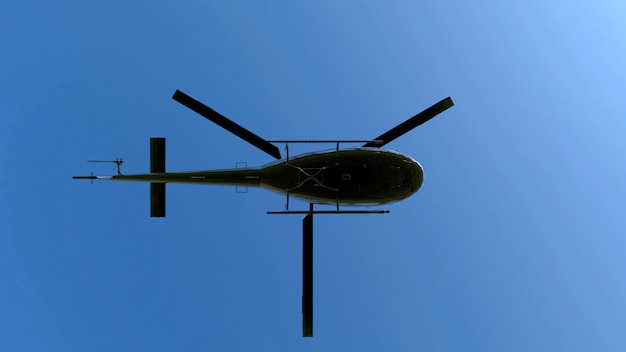 Low angle view of flying black metal helicopter on blue sky. Premium Photo