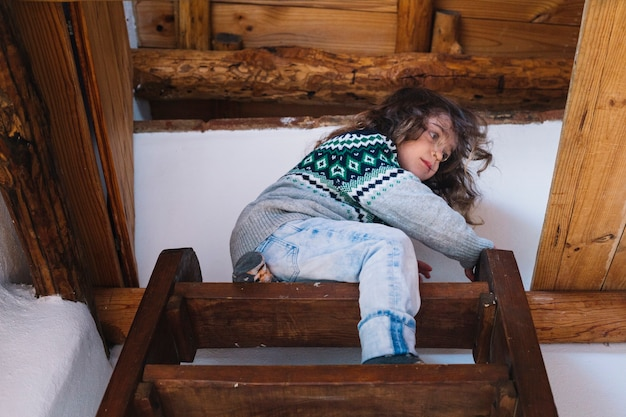 Low angle view of a girl sitting on top of the staircase Free Photo