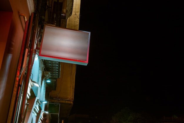 Low angle view of illuminated billboard on residential building against sky Free Photo