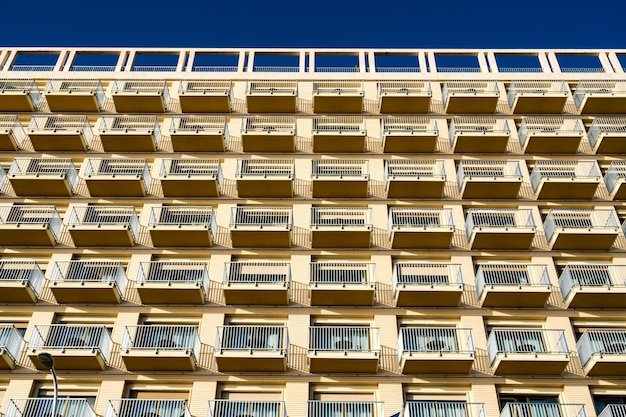 Inquadratura dal basso del moderno edificio con balconi contro il cielo blu Foto Gratuite