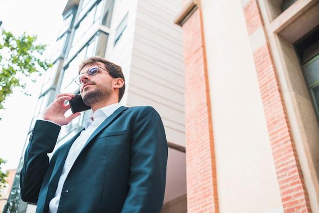 携帯電話で話している建物の下に立っている実業家の低角度のビュー 無料写真