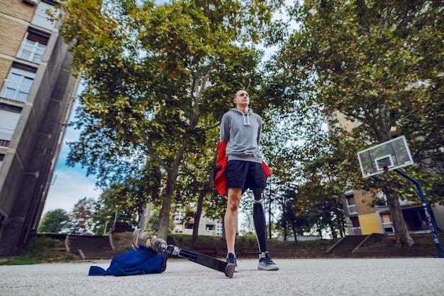 ハンサムな白人のスポーティな若い障害者の義足とバスケットボールコートに立っている間彼のトレーナーを脱いでスポーツウェアでの低角度のビュー。 Premium写真
