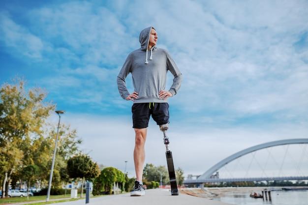 スポーツウェアと義足立っている川の横にある競馬場の腰に手で立っているスポーティな白人障害者の低角度のビュー。 Premium写真