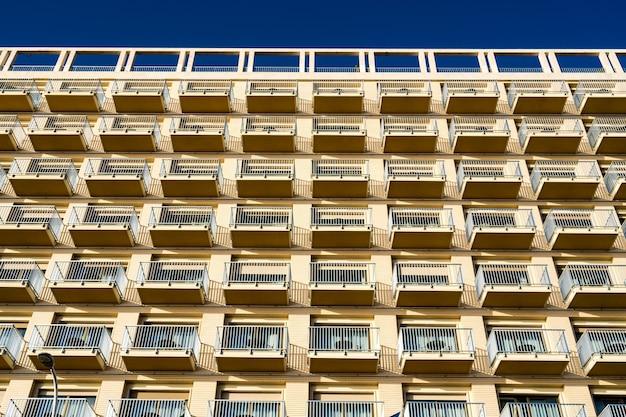 푸른 하늘을 배경으로 발코니가있는 현대적인 건물의 낮은 각도보기 무료 사진