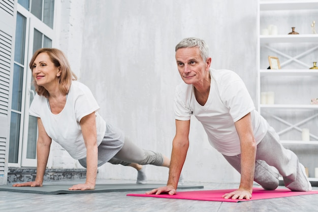 Low angle view of old couple doing pushups on mat at home Free Photo