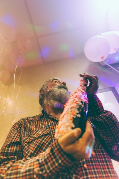 Low angle view of senior man holding alcohol bottle in hand decorated with confetti Free Photo