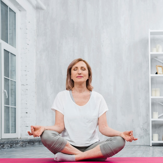 Low angle view of a senior woman doing meditation at home Free Photo