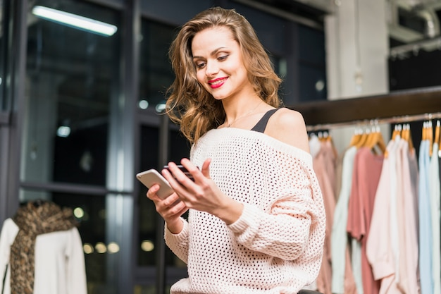 Low angle view of a stylish young woman using cellphone and gift card for shopping online Free Photo