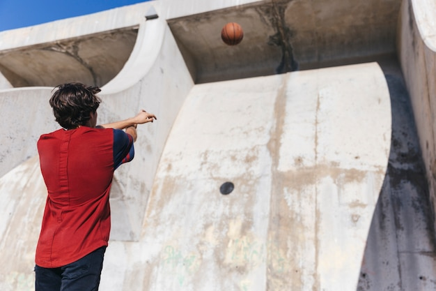 Low angle view of a teenage boy throwing basketball Free Photo