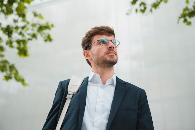 Low angle view of a young businessman standing against wall looking away Free Photo