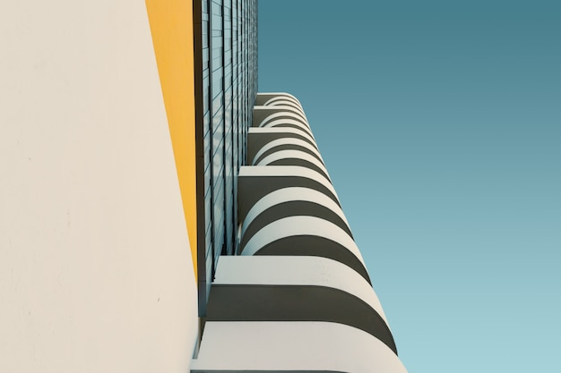 Low angle of a white concrete building under the clear blue sky Free Photo