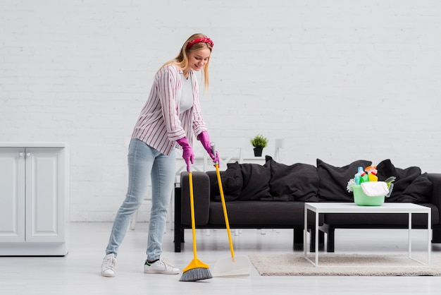 Low angle woman brushing floor Free Photo