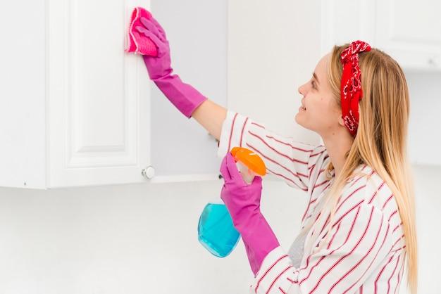Низкий угол женщина, уборка стен дома Premium Фотографии
