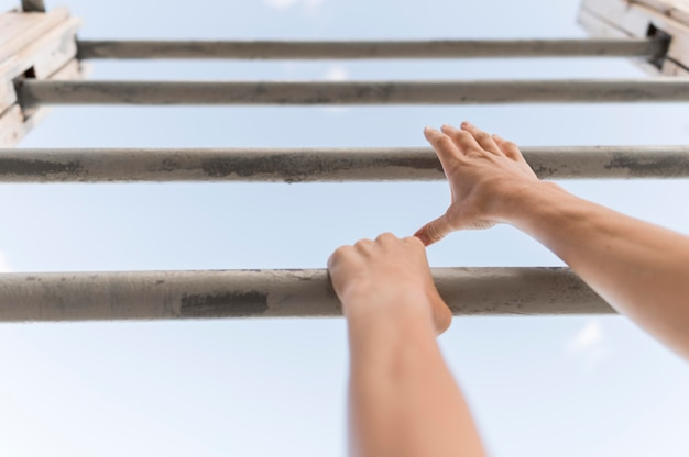 Low angle woman climbing on metal bars Free Photo