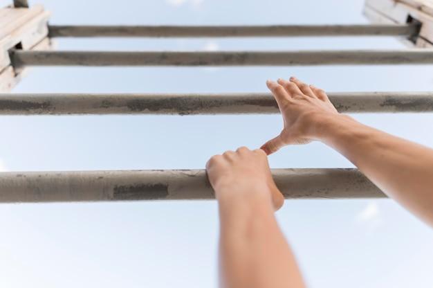 Женщина под низким углом, восхождение на металлические прутья Бесплатные Фотографии