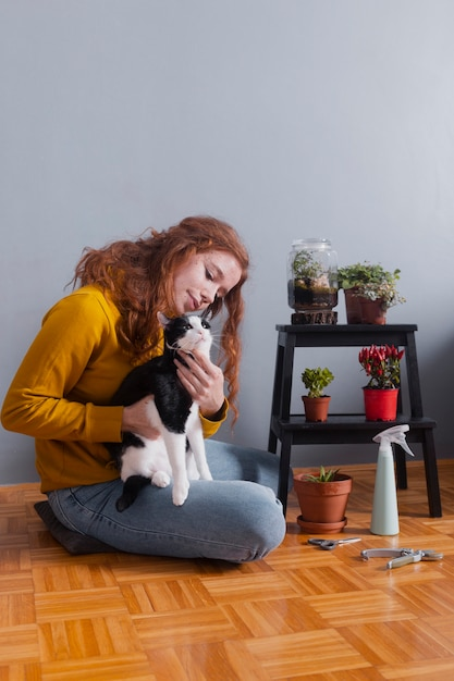 Low angle woman at home hugging cat Free Photo