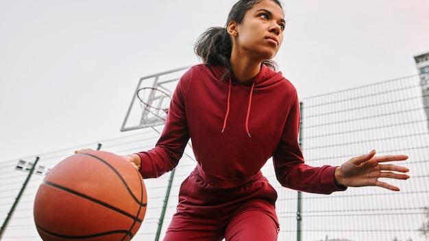Женщина с низким углом играет в баскетбол Бесплатные Фотографии