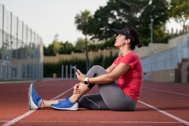 Женщина с низким углом отдыха после бега Бесплатные Фотографии
