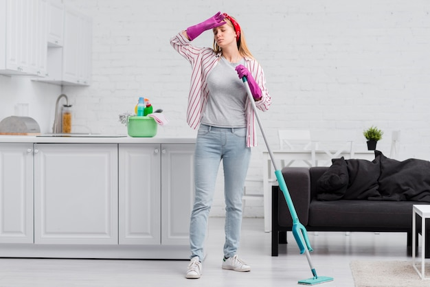 Low angle woman tired from cleaning Free Photo