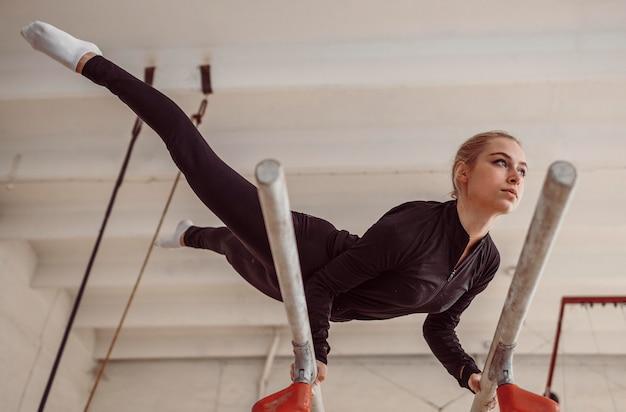 Тренировка женщины с низким углом для чемпионата по гимнастике Бесплатные Фотографии