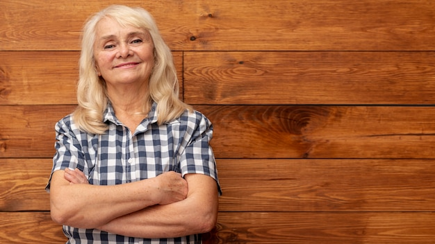 Low angle woman with wooden wall as background Free Photo