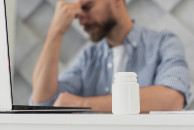 Low angle young man at office having headache Free Photo