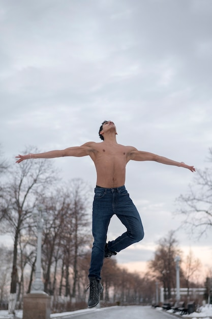 Low angle young man performing ballet outdoor Free Photo