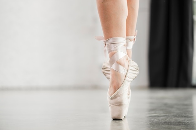 Low section of ballerina's leg in pointe shoes standing on floor Free Photo